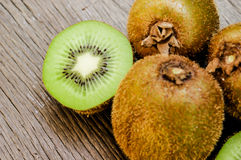 Some fresh Kiwi Fruits on an old wooden table. Some fresh Kiwi Fruits (selective focus) on an old wooden table, half of kiwi royalty free stock photography
