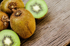 Some fresh Kiwi Fruits on an old wooden table. Some fresh Kiwi Fruits (selective focus) on an old wooden table, half of kiwi stock photography