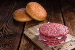 Some fresh made Burgers. (raw minced Beef) on an old wooden table Stock Image