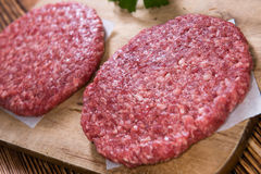 Some fresh made Burgers. (raw minced Beef) on an old wooden table stock images