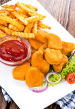 Some fresh made Chicken Nuggets (with chips). Some fresh made golden Chicken Nuggets with crispy chips Royalty Free Stock Photography