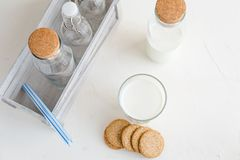 Fresh milk in bottles and in a glass. Almond or cow milk. White. Some fresh milk in glass bottles and decorated with kitchen napkin and a box-keeper Stock Photos