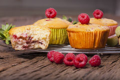 Some fresh Muffins. Some whole muffins and one bitten muffin on a cake wire rack with fresh raspberries on the front side Stock Photo