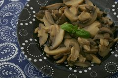 Fresh mushrooms. Some fresh mushrooms with basil on a black plate Stock Images