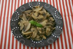 Fresh mushrooms. Some fresh mushrooms with basil on a black plate Stock Photos