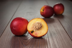 Some fresh nectarines over wooden background. Some fresh nectarines over brown wooden background Stock Photos