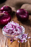 Some fresh Red Onions (diced). On an old wooden table Royalty Free Stock Image