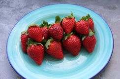 Some fresh strawberries. On a green plate royalty free stock image