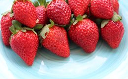 Some fresh strawberries. On a green plate royalty free stock images