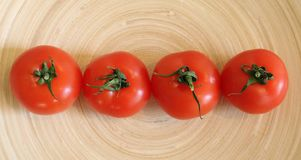 Some fresh tomatoes. A wooden plate royalty free stock photo