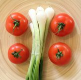 Some fresh tomatoes and spring onion. On a wooden plate stock image