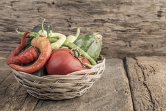 Some fresh vegetables in a basket. On wooden table royalty free stock photo