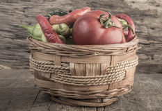 Some fresh vegetables in a basket. On wooden table royalty free stock photography