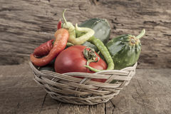 Some fresh vegetables in a basket. On wooden table stock images