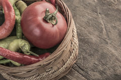 Some fresh vegetables in a basket. On wooden table royalty free stock image