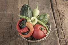 Some fresh vegetables in a basket. On wooden table stock photography