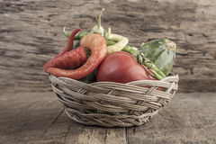 Some fresh vegetables in a basket. On wooden table royalty free stock images