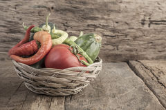 Some fresh vegetables in a basket. On wooden table stock image