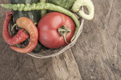 Some fresh vegetables in a basket. On wooden table stock photos