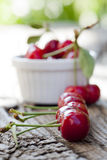 Some Freshly picked Cherries in a Row. Some Freshly picked ripe cherries in a row, in the background, out of focus more cherries in a bowl Stock Photo