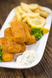 Some fried Fish Sticks (selective focus). On an old wooden table stock photo