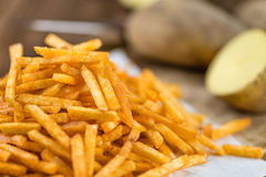Some fried Potato Sticks (close-up shot). On an old wooden table Royalty Free Stock Photo