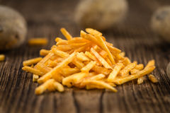 Some fried Potato Sticks (close-up shot). On an old wooden table Stock Image