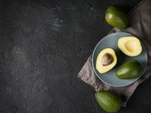 Some fruit of avocado whole and half on plate. Over dark bckground royalty free stock image