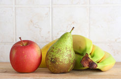Some fruit on a chopping board. A composition with a red apple, a pear and some bananas on a wooden chopping board, inside a kitchen, landscape cut Stock Images