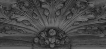 Some fruits with floral decoration. Shot in black and white detail of the sculpture on the facade of this historic building representing some characters / stock images