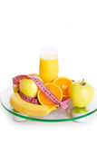 Some fruits, juice and measure tape on scales Royalty Free Stock Image