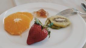 Some fruits in white dish. Strawberry orange kiwi and honey in white dish Stock Images