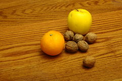 Some fruits on wooden table. Some european winter fruits, orange, apple and nuts on a wooden table Royalty Free Stock Photography