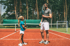Some fun before the game. Full length of little blond hair girl and her father wearing sports clothing and carrying tennis rackets in front of their faces while stock photo