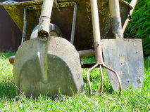 Some garden tools near an old wheelbarrow. Some garden tools near an old metal wheelbarrow Stock Photography