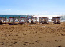 Some gazebos on a sandy beach. Some pavilions on a sandy beach royalty free stock images