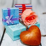 Valentine day gifts ready to present concept. Some gift boxes collected in a pile with a pink rose blossom and wooden heart pendant. Romantic gift, probably for Royalty Free Stock Photography