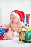 Some gifts from Santa. Baby in santa hat and some gifts Royalty Free Stock Images