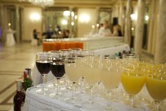 Some glasses filled with wine and juice on a front of reception. Some glasses filled with wine and juice to be filled with champagne at reception Royalty Free Stock Photography