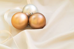 Some golden christmas balls on the white fabric. Golden christmas balls on the white fabric stock images