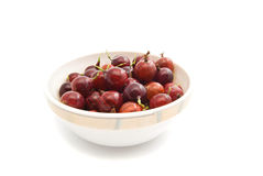 Some gooseberries on a glass dish. Tasty red gooseberries on a dish closeup on white Stock Photography