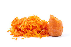 Some grated carrot and half. Isolated on the white background Royalty Free Stock Images
