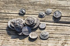 Some Greek metal ancient coins. Stack of various Greek ancient coins above wood background, Athens, Greece royalty free stock image
