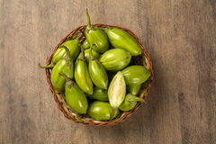 Some green african eggplants over a wooden surface Royalty Free Stock Image