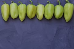 Some green bell peppers on grey background. Top view royalty free stock photo