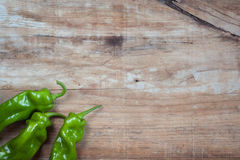 Some green pepers in old wooden background. Lifestile Stock Images