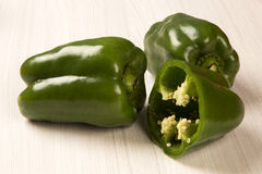Some green peppers over a wooden surface. Royalty Free Stock Photography