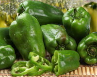 Some green peppers over a wooden surface. Stock Image
