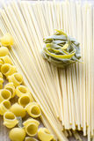 Some green raw pasta. Is on the yellow linguini Stock Photo