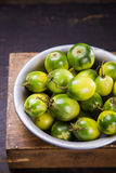 Some green tomatoes. In dish on wooden background Royalty Free Stock Photo